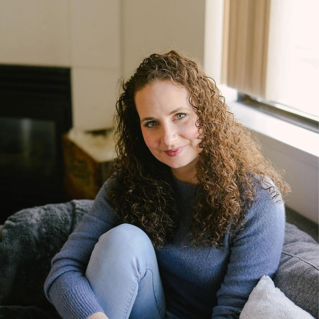 Emily Lycopolus Headshot Sitting on a grey couch
